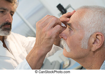 optometrist putting eye drops in senior patients eye