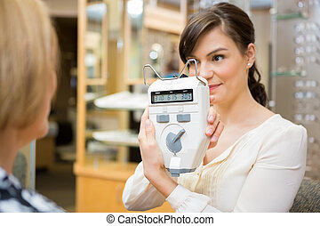Optometrist Showing Pupilometer To Mature Woman