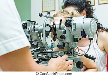 Optometrist with patient, giving an eye examination