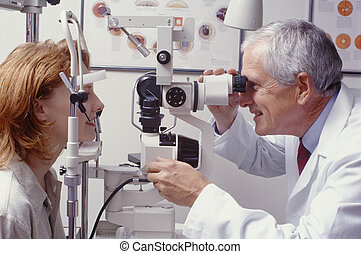 optometrist with patient, giving eye exam - optometrist with...
