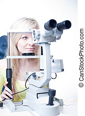 optometry concept - pretty young female patient having her eyes