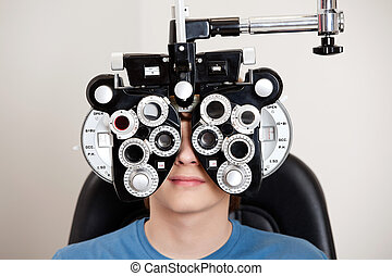 Optometry Exam - Boy sitting while undergoing an eye test...