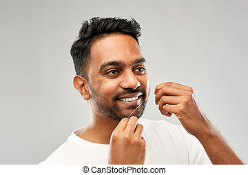 indian man with dental floss cleaning teeth