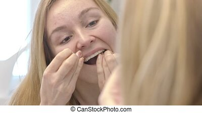 Oral hygiene and health care. Smiling women use dental floss...