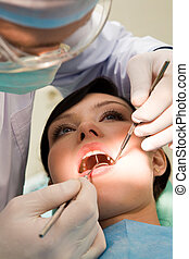 Oral hygiene - Close-up of woman with open mouth being...