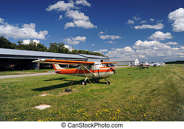 Orange airplane moored on the airfield
