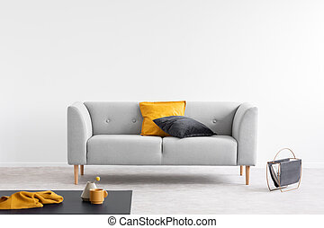 Orange and black pillow on grey couch in grey living room interior with copy space. Real photo