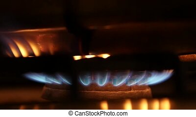 orange and blue flames of a gas stove in the dark