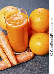 Orange and carrot juice in glass with ginger, fresh vegetables and fruits on wooden background