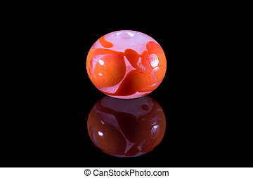 Orange and pink glass bead with reflection on black...