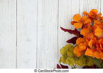 Orange and red fall flowers on weathered whitewash textured wood background with copy space for your fall or autumn message