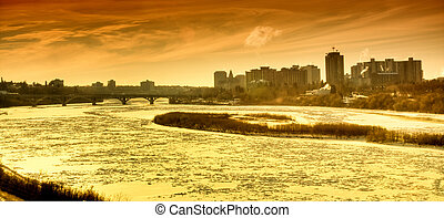 Orange and red glow of a Frozen river and cityscape at...