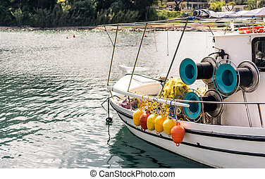 Orange and yellow buoys hanging from a side of a boat