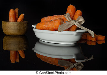 Orange baby carrot isolated on black glass