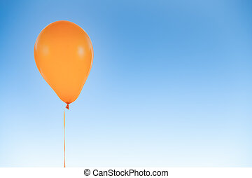 Orange balloon for birthday and celebrations isolated at blue sky