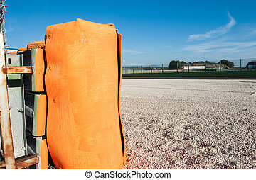 Orange barrier close up off the track on motor sport circuit with gravel safety space