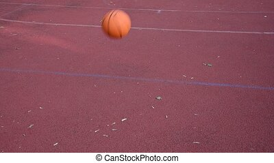 Close up orange colored unbranded basketball ball bounces over red outdoors court, high angle view, 4K