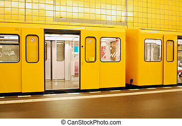 orange berlin metro train in a yellow station