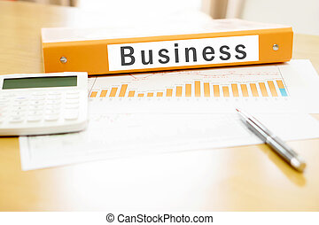 Orange  binder business on desk in the office with calculator and pen