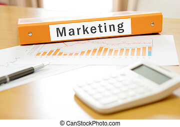 Orange  binder marketing on desk in the office with calculator and pen