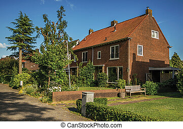 Orange brick house with beautiful and verdant garden in front of alley at Weesp.