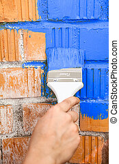 Orange brick wall painted with blue color