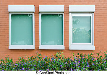 orange Brick wall with windows little plant and flower