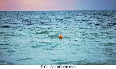 Orange buoy float floats in the sea. Overcast.