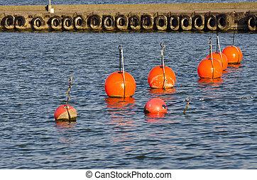 Orange buoy in sea on water