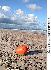 orange buoy on sea beach sand