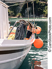 Orange buoys hanging from a side of a boat