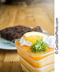 orange cake topped with piece of orange in plastic cup