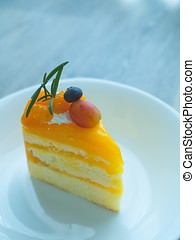Orange cake with topping mix fruit on white plate