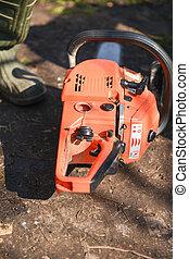orange chain saw in the garden. Ready to work
