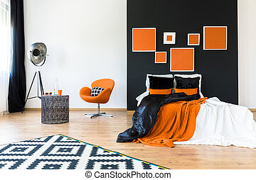 Orange chair in retro bedroom