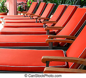 Orange Chairs - A row of orange chaise lounges in a solarium