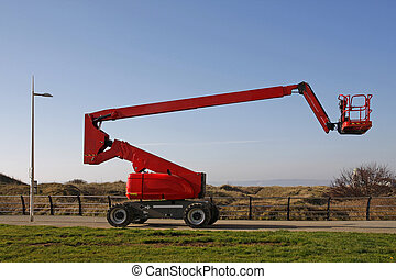 Orange cherry picker, side view against a blue sky