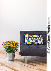 Orange chrysanthemums and gray sofa decorated with bright cushion.