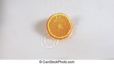 Orange, citrus sinensis, Slice Falling on Water and splashing, against White Background, Slow Motion