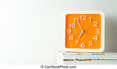 Orange clock on stacked book with white copy space wall