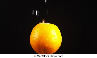 orange, close - up. Drops of water fall on a rotating apple on a black background. super slow-motion.