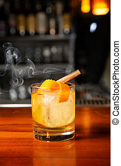 Orange cocktail with ice cube and orange zest.
