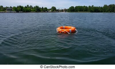 Orange color rescue buoy lifebuoy being thrown into water....