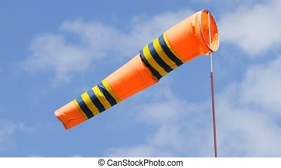 Orange color windsock in airport on the blue sky