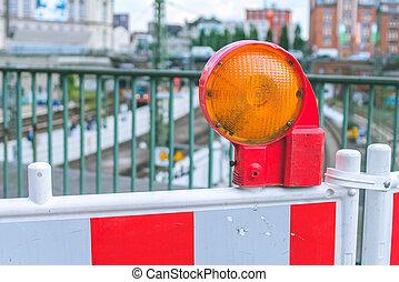 Orange construction warning street barrier light on barricade. Road construction on the streets of European cities. Germany. Hamburg