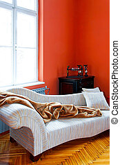 Orange living room corner with retro sofa