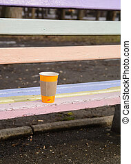 Orange cup with hot coffee forgotten on a wooden bench in the spring park.