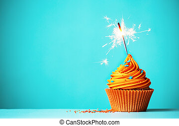Orange cupcake with sparkler and copy space to side