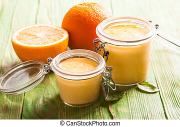 Orange curd in glass jars on the table