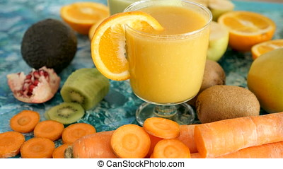 Orange detox smoothie on vivid background next to fresh...